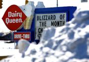 "A Dairy Queen sign advertises the ""Blizzard of the Month"" as piles of snow surround the parking lot in Sidney, Ohio. Much of Ohio was shut down Wednesday when snow and ice closed schools for a second day and many workers heeded warnings to stay off treacherous roads."