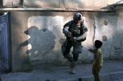 A U.S. soldier from the 5th Battalion, 20th Infantry Regiment of the Second Infantry Division greets a child in the Shaab neighborhood of Baghdad, Iraq. Troops were conducting a house-to-house search on Wednesday.