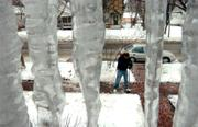 Viewed between the icicles on his front porch, Lawrence resident Aaron Blosser clears the sidewalk outside his Connecticut Street home Friday from a storm earlier this week - just in time for Friday's new snow.