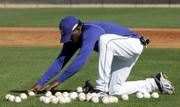 KANSAS CITY ROYALS INFIELDER ANGEL BERROA picks up balls following a workout in Surprise, Ariz. While Berroa got an early start on spring training Friday, the Royals officially open camp today with the pitchers and catchers reporting for duty.