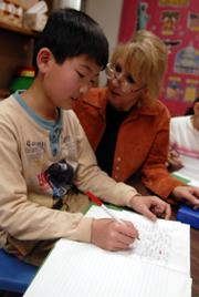 Gyong MIn Moon, 11, gets some special attention from his teacher Karen Ward, an English Language Learner intermediate instructor at Hillcrest School. The English as a Second Language program at Hillcrest has grown from 115 to 285 students in the past six years. Hillcrest serves more than half of the Lawrence school district's ESL students.