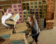 Kansas University Kappa Kappa Gamma sorority members Samantha Smith, Dallas sophomore, left, and Megan Hennessy, St. Louis sophomore, help sort cases of Girl Scout Cookies at the Douglas County 4-H Fairgrounds. The women were volunteering for their sorority Monday morning.