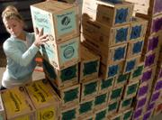 Molly McMahan, a KU freshman from Prairie Village and a Kappa Kappa Gamma sorority member, helps sort the 6,447 cases of Girl Scout Cookies delivered Monday at the Douglas County 4-H Fairgrounds community building. Area scout troops picked up the cookies for distribution Monday afternoon.
