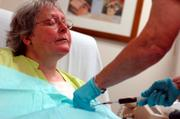 "With her eyes closed in a ""here we go again"" expression, Kathy's port, implanted in her chest, is flushed before her chemotherapy cisplatin is administered."