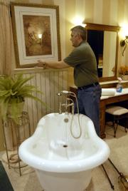 Mark Fiedler, of Custom Wood Products of St. Marys, sets up for the Lawrence Home Show at 5200 Clinton Parkway.