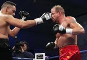 John Castle, left, throws a punch at Tommy Morrison. Morrison knocked out Castle on Thursday in Chester, W.Va.