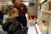 "Dylan McManis, 9, asks Sean Sawyer, a firefighter, questions about the Hazard House on Saturday at the Lawrence Home Show. ""We use the Hazard House to show kids some of the possible dangers in their home, like turning on a radio while in the bathtub or kids playing with matches,"" Sawyer said."