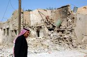 A man passes by a house destroyed in a suicide bomb attack in Ramadi, Iraq. A suicide bomber driving a stolen ambulance packed with explosives struck a police station Monday.