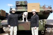 Col. Norb Jocz, left, and Sgt. Maj. James Savitski pose with Chester the bulldog and a new tank Friday at Fort Riley.