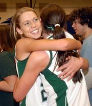 Free State's Jenna Brantley, left, hugs teammate Kelsey Harrison after the Firebirds' 36-30 victory over Lawrence High. The win Saturday in Olathe earned the Firebirds a trip to Class 6A state.