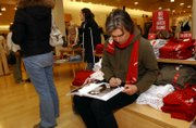 Bobby Shriver, Product (RED) co-founder and John F. Kennedy's nephew, signs a book  for Colleen Pesci Saturday at Gap, 643 Mass. The book is a (RED) Gap product. Product (RED) seeks to raise money for charitable causes by diverting a portion of the price of certain items.
