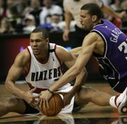 PORTLAND'S BRANDON ROY, LEFT, battles Sacramento's Francisco Garcia for a loose ball during Saturday's game. Roy is one of the favorites to win this season's Rookie of the Year award.