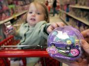 Charlotte LeBaron, 2, reaches for a Polly Wheel at a Target store. Mattel is combining dolls and cars in the first line of miniature die-cast racers just for girls. The cars are paired with the company's Polly Pocket dolls.