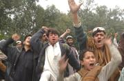 Afghan men shout anti-American slogans after a car bomber attacked an American convoy in eastern Afghanistan on Sunday. Following the bombing, witnesses said, U.S. troops opened fire on civilians, killing at least eight. Hundreds of Afghans gathered to protest the violence, blocking the road and throwing rocks at police.