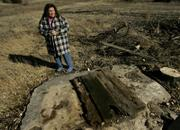 Robin Bailey stands by a dried-up, abandoned well on her farm near Stockton last month. Bailey blames nearby irrigation wells for drying up bodies of water on her farm.