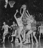 Kansas University sophomore Wilt Chamberlain (13) struggles to draw a rebound away from a crowd of players during the 1957 National Championship game.