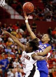 Kansas guard Shaquina Mosley, right, shoots the ball over Oklahoma State guard Andrea Riley. Mosley scored 18 points in the Jayhawks' 71-62 victory Tuesday in Oklahoma City.