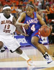 KANSAS UNIVERSITY FRESHMAN FORWARD DANIELLE MCCRAY drives the ball past Oklahoma State forward Rashidat Sadiq during the second half of the teams' opening-round game at the Big 12 Conference Tournament. McCray scored 16 points, including a crucial three-pointer late in the contest, as KU earned a 71-62 victory Tuesday and a spot in today's quarterfinals against Baylor.