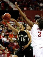 Oklahoma players Ashley Paris, center, and Courtney Paris, right, try to block the shot of Baylor guard Jhasmin Player (15). Baylor upset Oklahoma, 78-64, Thursday in Oklahoma City.