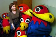Rebecca Schulte, archivist with University Archives, shows off some retired Jayhawk and Baby Jay mascot costumes tucked away in Spencer Research Library. The items are an example of some of the unusual pieces collected by University Archives.