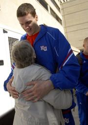 Kansas University men's basketball player Sasha Kaun gets a hug Thursday from Jayhawk fan Nancy Harmony.