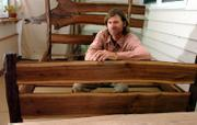 Mark King shows off a bed he made recently from rustic walnut. King will be showing and selling his handmade furniture during the Spring Arts & Crafts Festival today at the Douglas County 4-H Fairgrounds, 21st and Harper streets. The event, which will feature 81 exhibitors, is scheduled from 9 a.m. to 4 p.m.