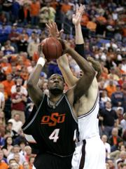 Oklahoma State forward Mario Boggan (4) goes up for the winning basket against Texas A&M's Antanas Kavaliauskas. Seventh-seeded OSU eliminated second-seeded A&M, 57-56, Friday in Oklahoma City.