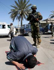 Iraqi army soldiers patrol as a man prays on the street in Baghdad, Iraq, on Sunday. A suicide car bomber rammed a truck carrying Shiite pilgrims returning from a major religious commemoration Sunday, killing at least 32 people a day after Iraqi leaders warned sectarian violence could eventually spread around the region.