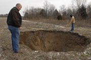 Murray Balk, left, and Randy Johnson measure a 30-feet wide sinkhole caused by undermining in Rick Schultz's field in Southeast Kansas.  Abandoned sub-surface coal mines are collapsing, causing sinkholes and large ground collapses that often times lead to voids hundreds of feet deep throughout the tri-state mining district in southeast Kansas.
