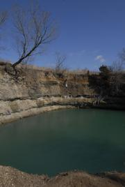 During the summer months, kids flock to this sinkhole filled with water north of Treece, Kan., and rope swing off the tree at upper left.  Health officials worry about the long-term effects of exposure to the water filling these abandoned mines.