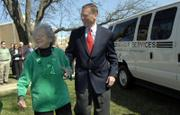 Lauraine Mulally, Lawrence, and her son, Ford Motor Co. CEO Alan Mulally, greet friends Friday at the Lawrence Senior Center. Alan Mulally presented a Ford van, right, to Douglas County Senior Services Inc. in honor of his mother. Alan Mulally will be the grand marshal in today's St. Patrick's Day Parade.