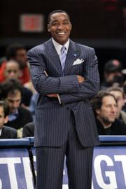 NEW YORK KNICKS COACH ISIAH THOMAS smiles while watching his team's game against the Miami Heat. Thomas received a contract extension even as his team struggles to stay in the Eastern Conference playoff hunt.