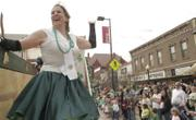 "Teresa Shock, Olathe, waves to the crowd on Massachusetts Street during Saturday&squot;s St. Patrick&squot;s Day Parade. Shock was one of six ""saloon girls"" on the Red Lyon Tavern&squot;s float."