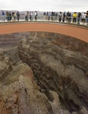 People walk on the Skywalk during the First Walk event Tuesday at the Grand Canyon on the Hualapai Indian Reservation at Grand Canyon West, Ariz. The Skywalk opens to the general public March 28.