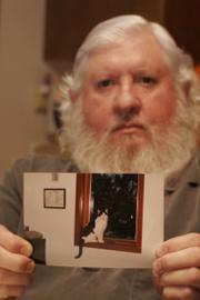Charles Bloss of Lecompton displays a photograph of his cat, Patches, who fell ill after consuming cat food that later was included in a national recall.