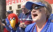 Barbara Lauter, Lawrence, sings along with the basketball band during a pregame pep rally Thursday afternoon in downtown San Jose. With Lauter is her boxing Jayhawk puppet 'Rocky Hawk.'