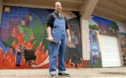 David Loewenstein, a local muralist, stands by one of his works at Hobbs Park ballfield in East Lawrence. Loewenstein and leaders of the Spencer Museum of Art at Kansas University hope the city will approve a downtown mural project to honor black artists from Kansas, such as Langston Hughes and Gordon Parks.