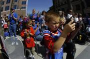 Young Jayhawk fan Kadin Louthan, 8, Henderson, Nevada, reviews his photographs from his digital camera during Saturday's pep rally in downtown San Jose.