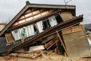 A man goes up a collapsed house to check its damage following Sunday's earthquake in Wajima, Ishikawa prefecture (state), northern Japan today. A powerful quake tore into a rural area of coastal central Japan on Sunday, killing at least one person as it toppled aging farmhouses and temples, set off landslides and caused a small tsunami. Some 170 people were injured.