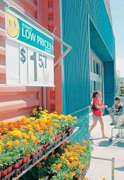A shopper leaves the Wal-Mart on Iowa Street this summer. Wal-Mart will have two stores in Lawrence because city commissioners struck a deal in August with the discount store earlier this year to build a store at the corner of Sixth Street and Wakarusa Drive.