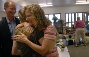 Pam Shanks, Raintree Montessori preschool teacher and special education coordinator, hugs her daughter Caitlin, 19, and husband, Craig Shanks, after receiving one of three Mayor's Excellence in Education Awards on Monday morning in her classroom at the school. Mayor Mike Amyx made a surprise visit to Shanks' classroom to present the award, joined by her family and other faculty members from the school.