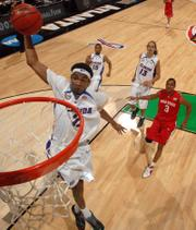 Florida's Corey Brewer goes up for a dunk as Ohio State forward Ivan Harris (3), Florida's Walter Hodge (15) and Joakim Noah (13) watch during the first half of the Final Four basketball championship Monday at the Georgia Dome in Atlanta.