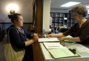 Amanda Mayhew, 23, Lawrence, receives instructions on filling out her advance voting ballot from voting clerk Marilyn Neuenswander at the Douglas County Courthouse. Mayhew, a student at Azusa Pacific University in Azusa, Calif., voted Monday while home for spring break.