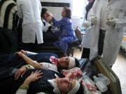 Girls in school uniforms lie at a hospital bed in Kirkuk, Iraq, 180 miles north of Baghdad. A suicide truck bomber targeted a police station in the oil-rich northern city on Monday, killing at least 15 people and wounding dozens, including many children from a nearby school, police said.