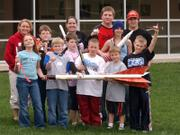 Eudora High School students from the Aerospace Alliance stand with some third- through eighth-graders who attended a rocket-building workshop on Saturday. The students display a model rocket along with the rockets they made at the workshop.