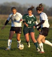 Lawrence High's Kaela Severa (7) and Olivia Dykes, right, double-up on Free State's Grace Lang (18). The teams played to a 1-all, double-overtime tie Tuesday at the Youth Sports Inc. fields.