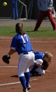 KU's Val Chapple, left, makes a throw to first base over the head of pitcher Valerie George in the first game of the Jayhawks' doubleheader with Arkansas. KU won the opener, 4-2, but lost the nightcap, 6-1, Tuesday at Arrocha Ballpark.