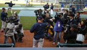 Boston pitcher Daisuke Matsuzaka walks out of the dugout as a crowd of Japanese and American media cover his entrance before the Royals' 7-1 loss Wednesday. Matsuzaka will make his major-league debut tonight.