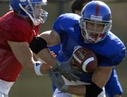 Kansas University running back Jake Sharp, right, takes a handoff from quarterback Todd Reesing. The Jayhawks practiced Wednesday on their practice fields.