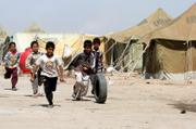 Iraqi children play with a tire in a refugee camp near Najaf, Iraq, 100 miles south of Baghdad. Some 600 people from Baghdad and surrounding areas have moved to the camp to escape sectarian violence. On Wednesday, a group of Shiite shepherds was kidnapped in a Sunni area west of the capital.